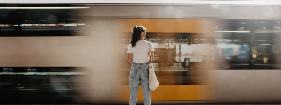 Frau vor vorbeifahrenden Zug